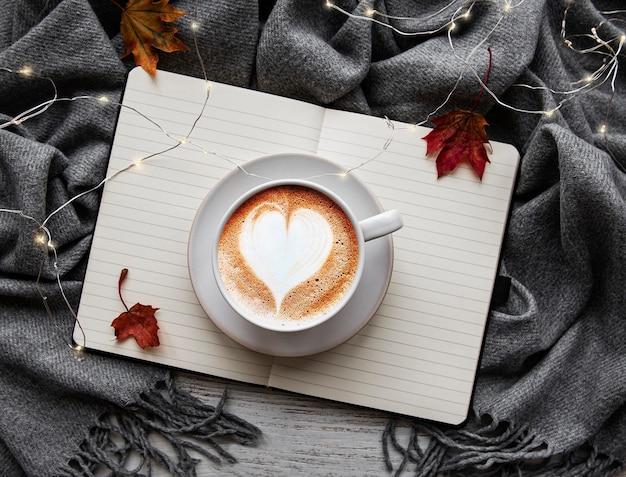 Hojas de arce, cuaderno, taza de café y bufanda. concepto de otoño o invierno. endecha plana, vista superior