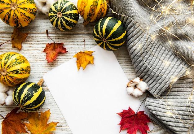 Hojas de arce otoñal, calabazas y bufanda de lana sobre un fondo de madera. fondo de otoño.