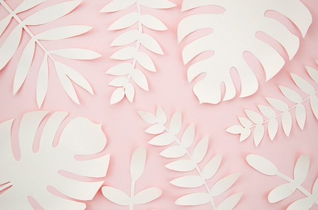 Hojas artificiales estilo de corte de papel con fondo rosa