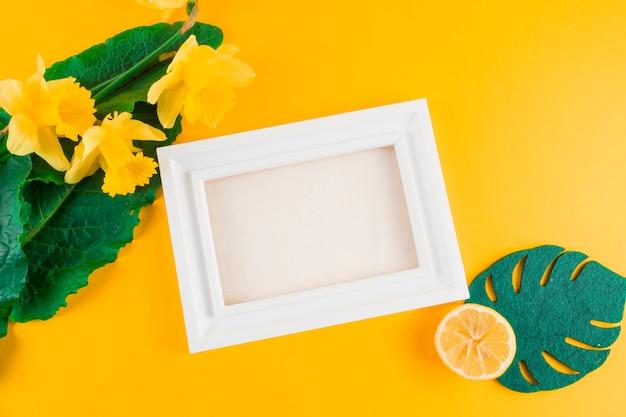 Hojas artificiales; flores de narciso; limón cerca del marco blanco sobre fondo amarillo