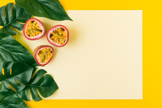 Hojas artificiales con frutos de la pasión contra papel en blanco sobre fondo amarillo.