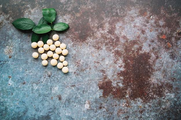 Hojas y bolas de chocolate blanco sobre fondo rústico grunge