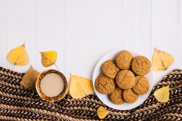Hojas y bufanda cerca de galletas y bebidas