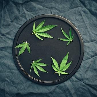 Hojas de cannabis, mariuana de diferentes tamaños en plato negro
