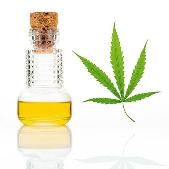 Hojas de cannabis verde con una botella de vidrio de reflexión de aceite de cannabis aislado en blanco