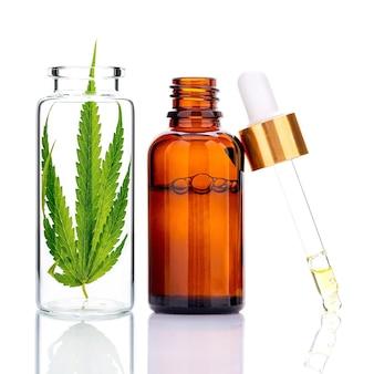 Hojas de cannabis verde con botellas de aceite esencial y reflejo de aceite cuentagotas aislado en blanco