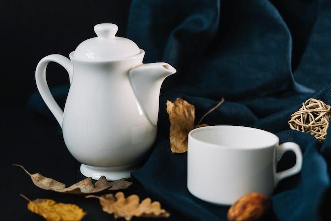 Hojas cerca de tetera y taza