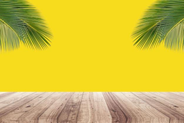 Hojas de coco sobre fondo amarillo para mostrar productos.