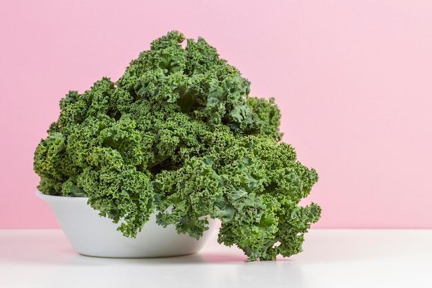 Hojas de col rizada verde orgánica cruda fresca de col rizada en un plato blanco con fondo de color rosa Foto Premium