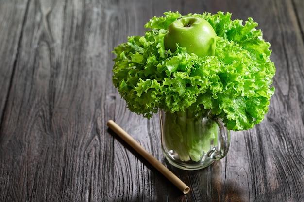 Hojas de ensalada, manzana verde en una jarra en la mesa de madera lista para cocinar un batido saludable