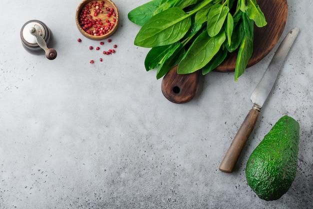 Hojas de espinaca cruda fresca sobre un soporte rústico de madera sobre una superficie de hormigón viejo gris. ingredientes para ensalada
