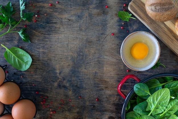 Hojas de espinaca tierna fresca en un cuenco y huevos sobre una mesa de madera. vista superior. copia espacio
