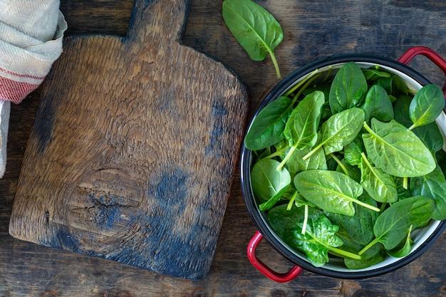 Hojas de espinaca tierna fresca en un recipiente sobre una mesa de madera rústica. copia espacio
