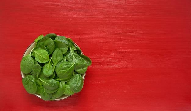 Hojas de espinacas frescas en plato blanco.