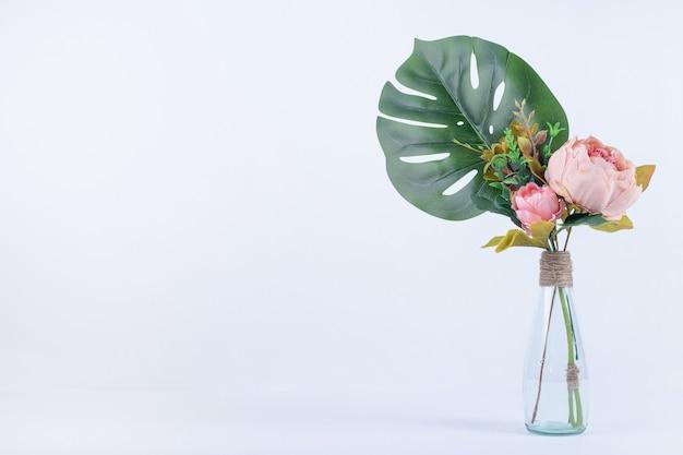 Hojas y flores artificiales en frasco de vidrio sobre superficie blanca.