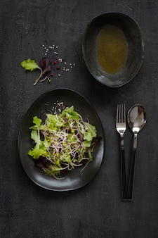 Hojas frescas de la ensalada del bebé, brotes color de rosa orgánicos de china con aceite de oliva en fondo oscuro