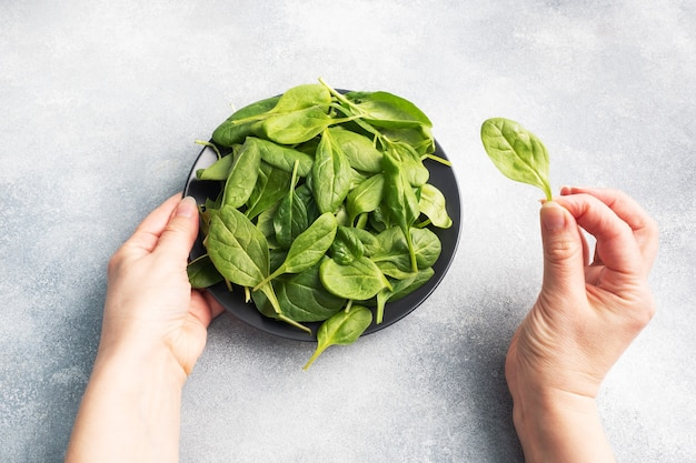 Hojas frescas de espinaca verde en un plato negro. manos femeninas sosteniendo un plato y una hoja de espinaca en la mano.