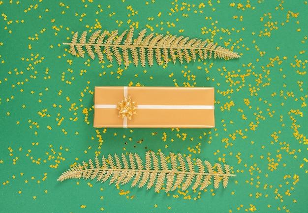 Hojas de helecho dorado y cajas de regalo sobre un fondo verde con estrellas doradas brillantes