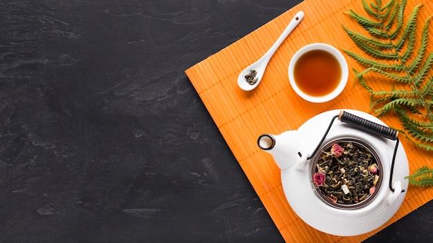 Hojas de helecho y hierba de té seca con tetera en mantel naranja sobre fondo negro