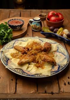 Hojas de khingal con cebolla frita y pollo.