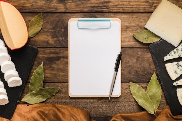 Hojas de laurel; queso; paño; bolígrafo y portapapeles en escritorio de madera