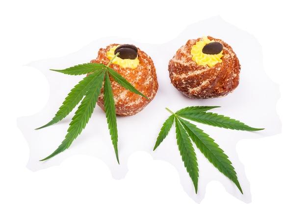 Hojas de marihuana y cupcakes con thc aislado en pared blanca.