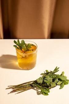 Hojas de menta con copa de cóctel en mesa blanca