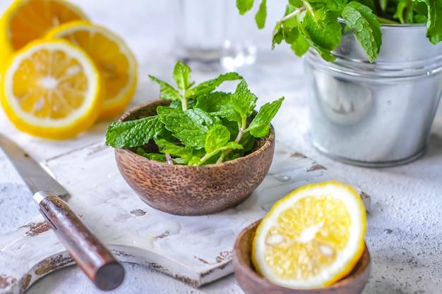 Hojas de menta fresca en una tabla de cortar con un cuchillo y limón