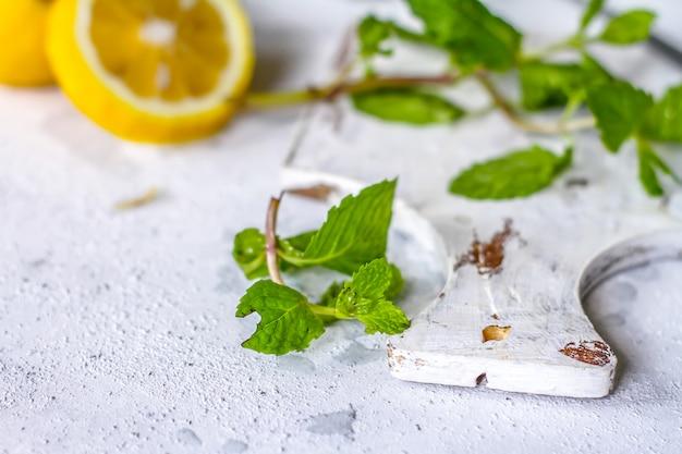 Hojas de menta fresca en una tabla de cortar con limones