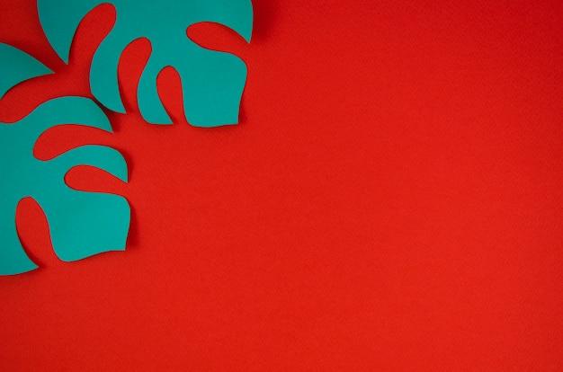Hojas de monstera azul con fondo rojo