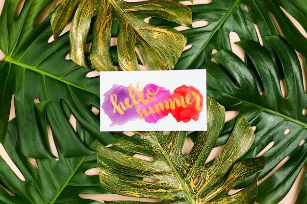 Hojas de monstera y cartel con letras de mano hola verano. concepto de verano, flatlay, fondo pastel
