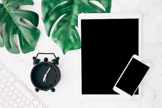Hojas de monstera verde; despertador; teclado; tableta digital y teléfono móvil sobre fondo texturizado.