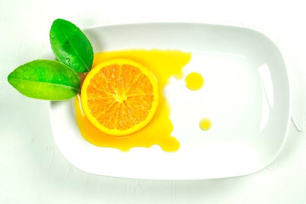 Hojas de naranja rodajas de naranja y zumo de naranja extendiéndose en un plato blanco