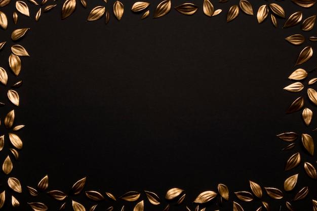 Hojas de oro sobre fondo negro espacio de copia