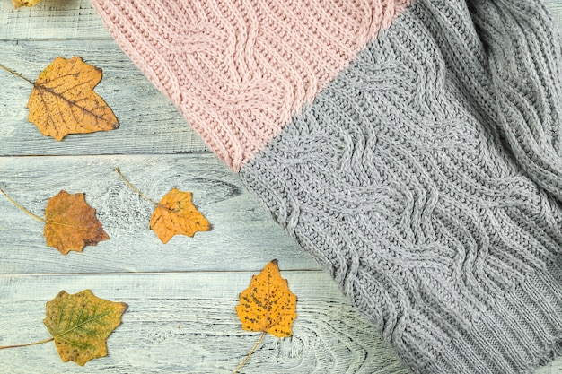 Hojas de otoño amarillas sobre un viejo fondo de madera con textura con una chaqueta con textura