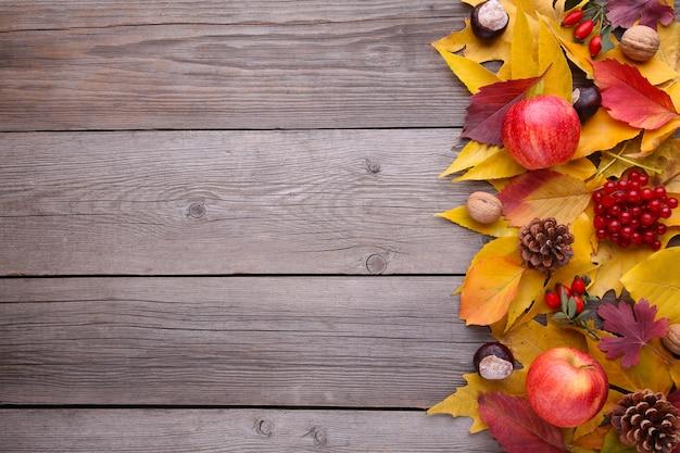 Hojas de otoño con bayas y frutas sobre un fondo gris
