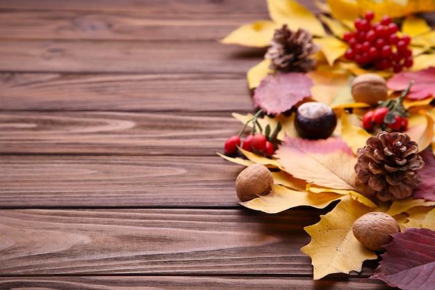 Hojas de otoño con bayas sobre un fondo marrón