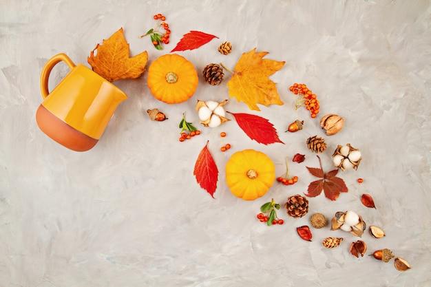 Hojas de otoño, calabazas, bayas se vierten de una jarra sobre un fondo gris