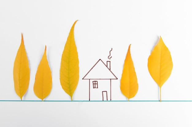 Hojas de otoño con casa pintada en blanco