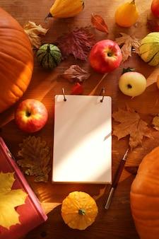 Hojas de otoño, cuaderno, manzanas y calabazas.