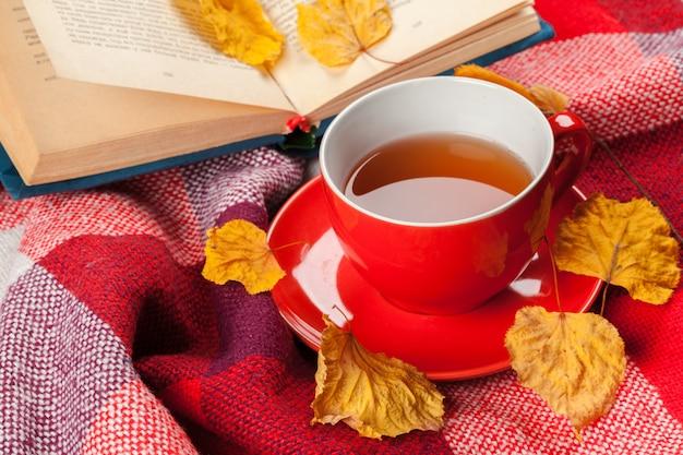 Hojas de otoño, libro y taza de té.