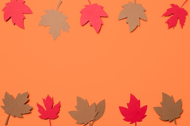 Hojas de otoño de papel plano sobre fondo naranja con espacio de copia