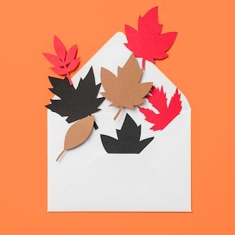 Hojas de otoño de papel en sobre sobre fondo naranja