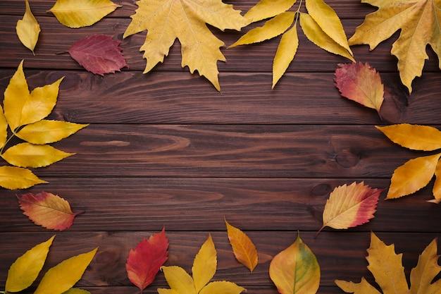 Hojas de otoño rojas y anaranjadas en mesa marrón