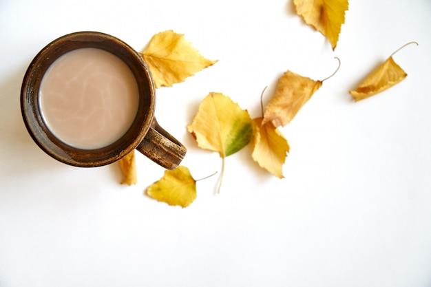 Hojas de otoño con taza de café o té en blanco