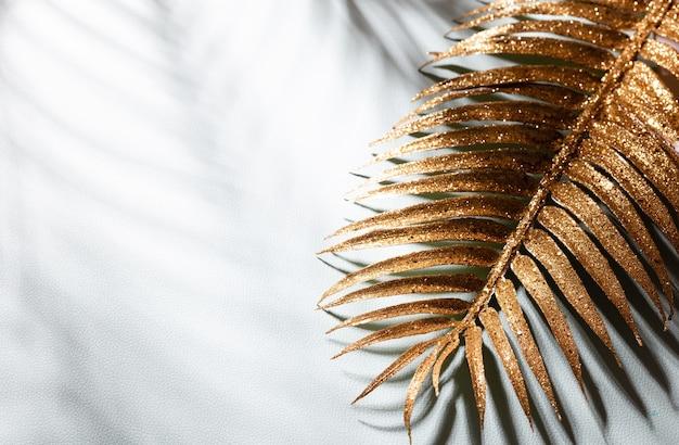 Hojas de palma doradas y sombras sobre un fondo de pared azul.