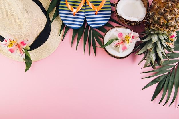 Hojas de palma tropicales, sombrero, zapatillas, piña, coco sobre fondo blanco.