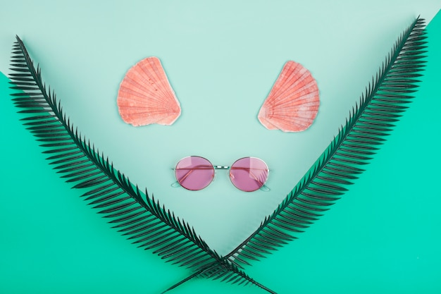 Hojas de palmera cruzadas decorativas; vieira y gafas de sol sobre fondo de menta