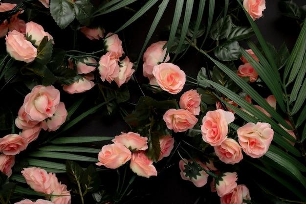 Hojas de palmera con fondo de flores rosas