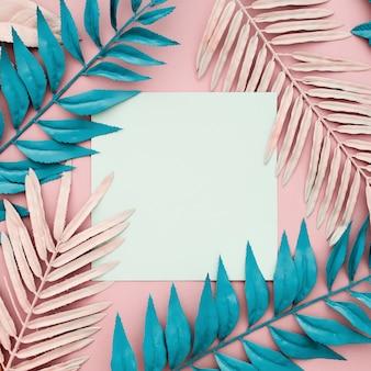 Hojas de palmeras tropicales con papel blanco en blanco sobre fondo rosa